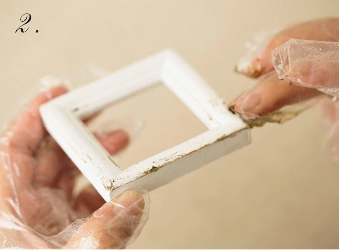 呈現掉漆效果,製作出陳舊的藝術相框 以蠟漆於白色相框塗抹出污漬,展現陳舊質感。 英文報紙先以咖啡液染色,染出舊紙的色彩。 使用正方形的相框營造出成熟的氣氛。 Tools 牛奶漆、蠟漆、即溶咖啡粉、熱水、拋棄式手套、容器、剪刀、立可帶式雙面膠帶  手指沾取適量牛奶漆,塗抹至外框,靜置乾燥。  待1乾燥後,手指沾取少量蠟漆,以邊緣為中心塗抹出污漬。  剪下英文報紙,放入咖啡液(即溶咖啡粉1小匙與熱水50攪拌混合)浸泡五分鐘。 等報紙呈現舊紙顏色後即可撈起晾乾,最後在背面黏上雙面膠帶。  在相框上塗抹3中的咖
