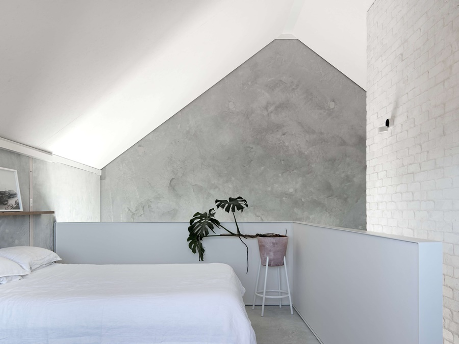 03-The-master-bedroom-is-done-with-concrete-and-brick-walls-a-lilac-half-wallm-which-adds-color-and-a-lilac-planter.jpg